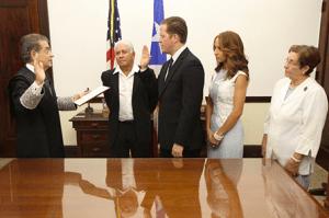 El Secretario de Estado, Hon. David Bernier, presta juramento ante el Juez Presidente del Tribunal Supremo, Hon. Federico Hernández Denton. Le acompañan su esposa, Alexandra Fuentes, y sus padres.
