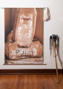 Mop Figure [Lean In] (Aldrich), paper, acrylic, oil, silicone, and found plastic, 2017, and Push Mower (Weissberger), digital photograph/print on fabric, mop, broom handle, 2016.