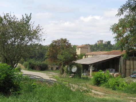 A farm building with a large roof and the ruin of Lagarde chateau beyond