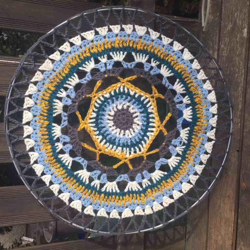 A second mandala made of white, blue, grey, peacock blue, and yellow yarn and fixed within a metal hoop to make a circle.