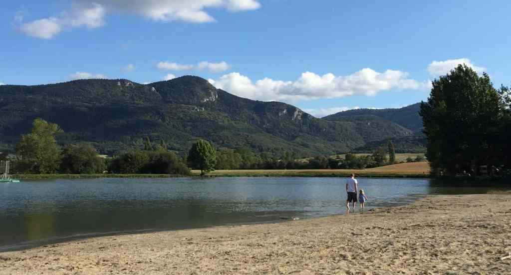 father and daughter walk along the edge of the water at the puivert swimming lake