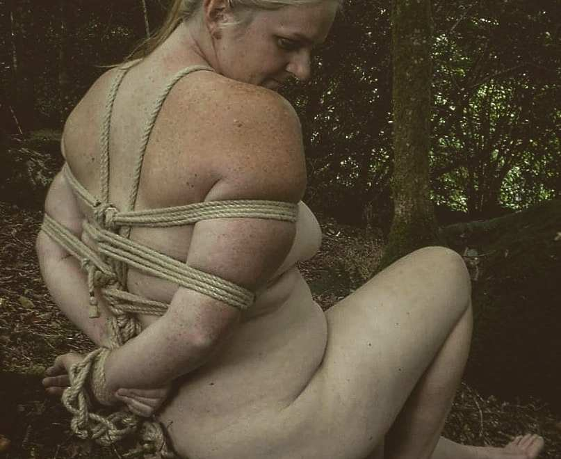 I am sinfully me header image. Me naked, bound in a low hands TK, sitting on a mossy tree stump.