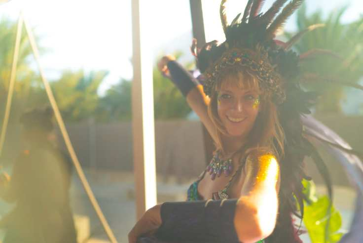 woman wearing blue spaghetti strap top with feather headdress