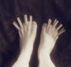 Two bare feet with a peg pinched in the skin between each of the toes.