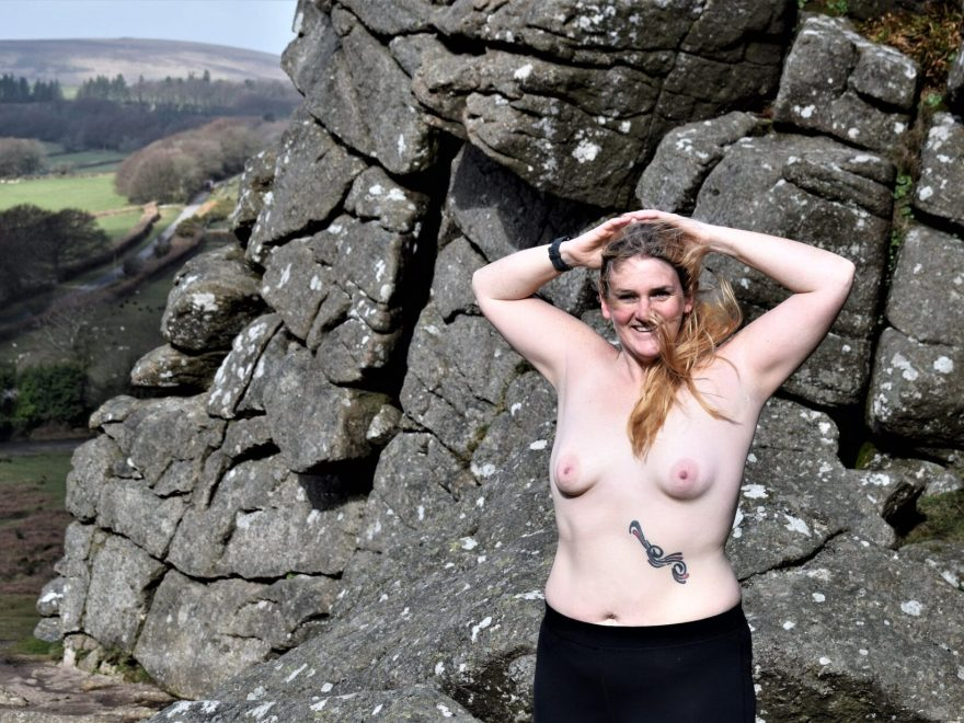 Topless lady standing on top on Hound Tor on dartmoor. Hands behind her head, wind swept hair and the biggest grin on her face