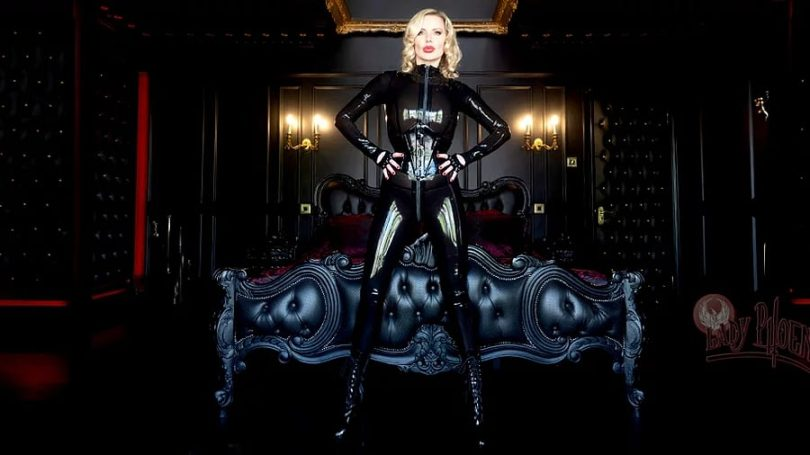 elust 138 header image of lady phoenix in a smokey latex catsuit standing hands on hips in front of an ornate bed.