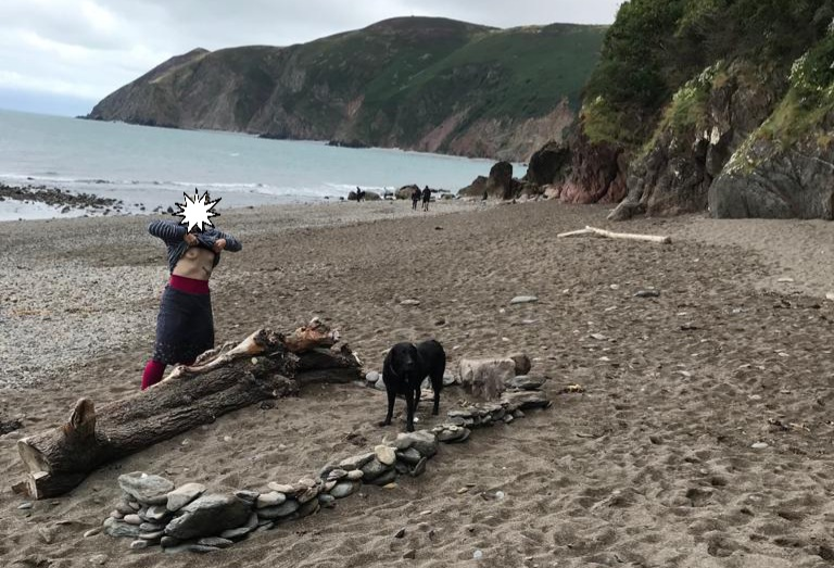 No local driftwood header of the barefoot sub pulling her jumper up to expose her breasts on a cold beach beside a large piece of driftwood.