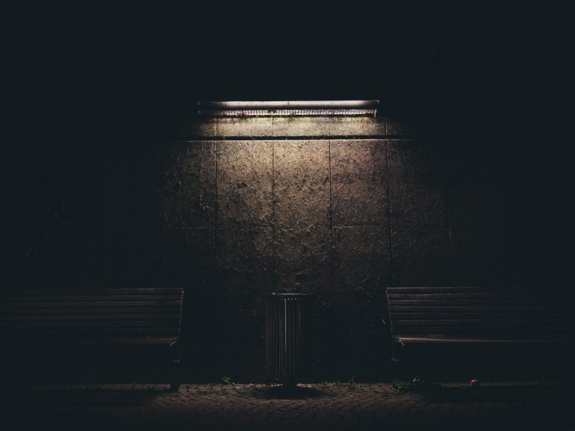A dark brick wall, a bin in the middle with a bench either side, illuminated from above by a single lightsource.
