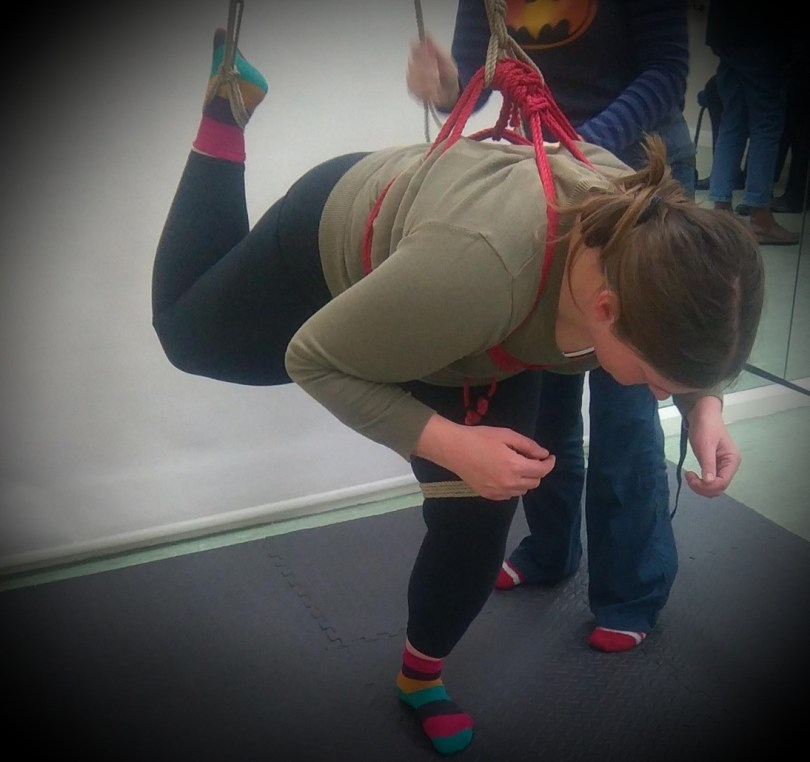 A little down time required header image shows a fully clothed barefoot sub in socks, in a chest harness, transitioning to a full suspension at peer rope group.