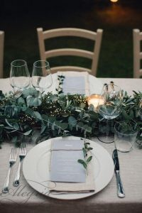 wedding-trends-2019-white-burlap-tablecloth-and-greenery-eucalyptus-table-runner-with-candles-duepunti-wedding-photography