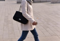 trendy woman with bag and phone walking