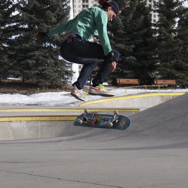 Adam jumps and flips his board before a slope in Shaw Millennium Park in Calgary, Alta., on Friday, March 5, 2021. Adam is an avid and consistent skateboarder. He and many other skateboarders skate on the sunny Calgary afternoon. (Photo by Alejandro Melgar/SAIT)