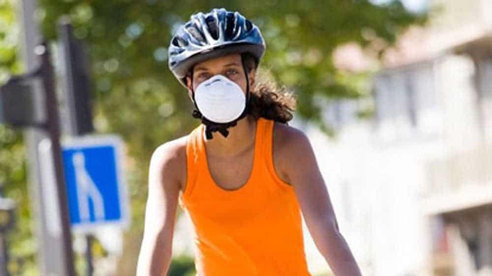 Kolesarska z obrazno masko opravlja kolesarski trening