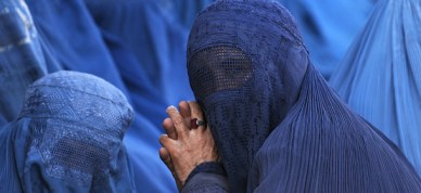 Afghan women sit on the ground as they w