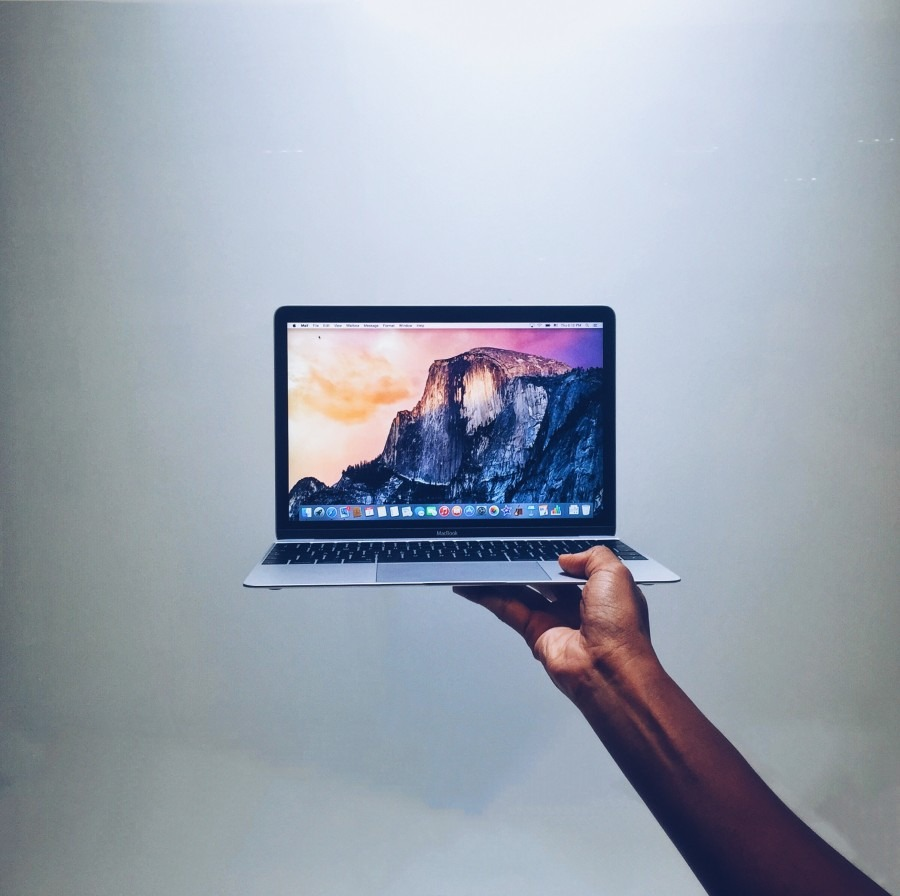 Hand holding a MacBook