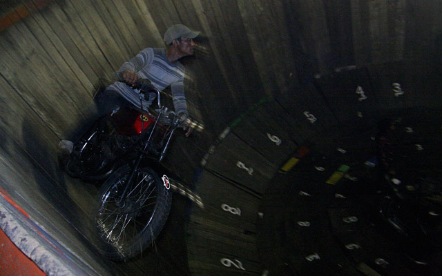 motorbike stunt, riding in a closed barrel wall