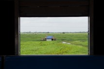 Hut in the middle of a vast green field in one of the villages along Circular Train route.