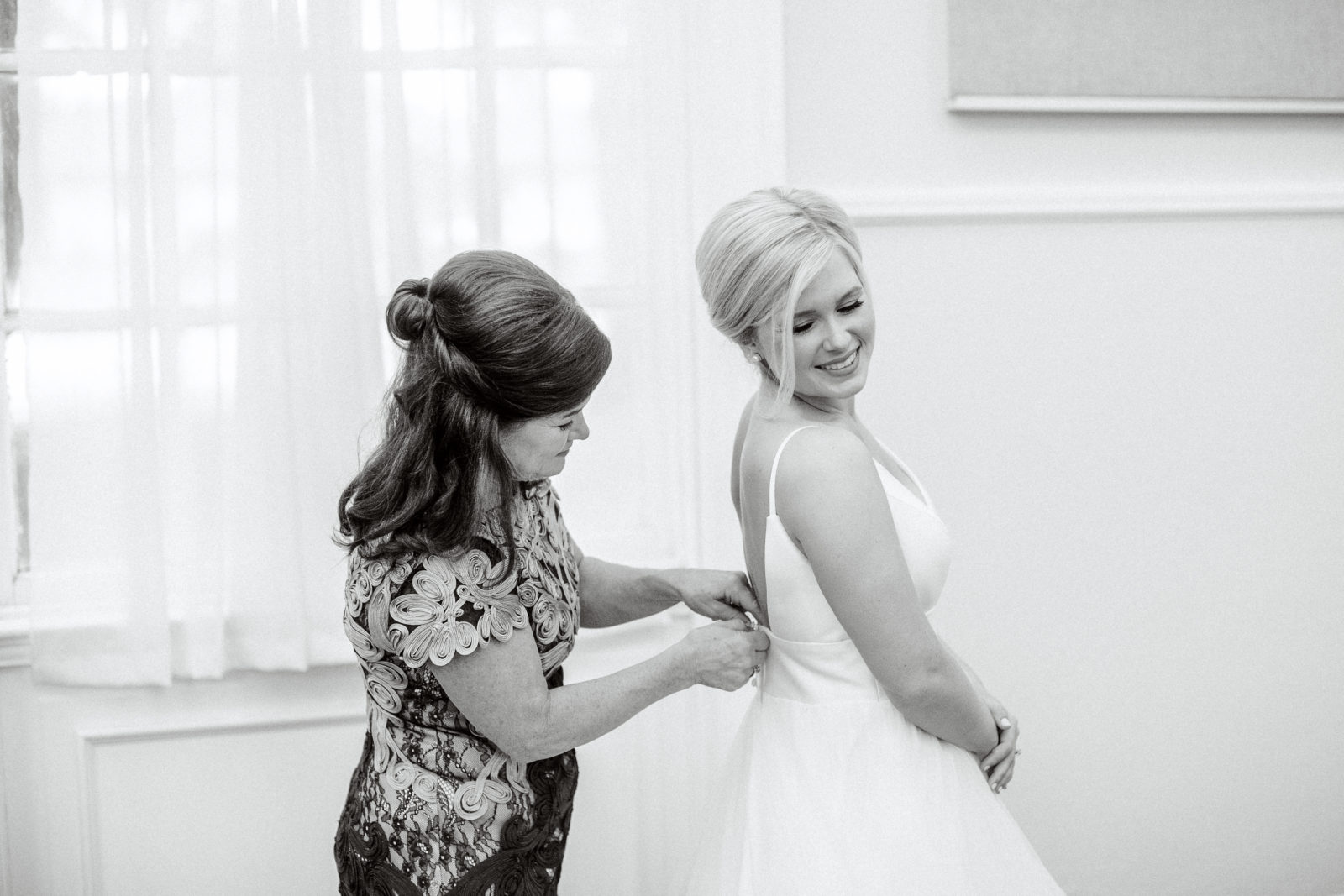 Mother of the bride helping bride into Bridal Boutique wedding gown