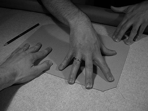 Drei Hände halten eine Schablone