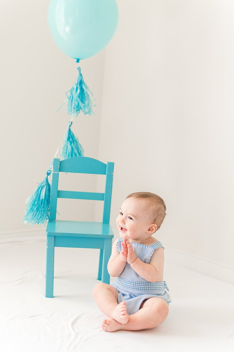One Year Cake Smash Portrait Session.  This cake smash session was complete with blue balloons, streamers, and a classic clean white background.  Styled in blue gingham romper and a blue bloomer this session is all precious!