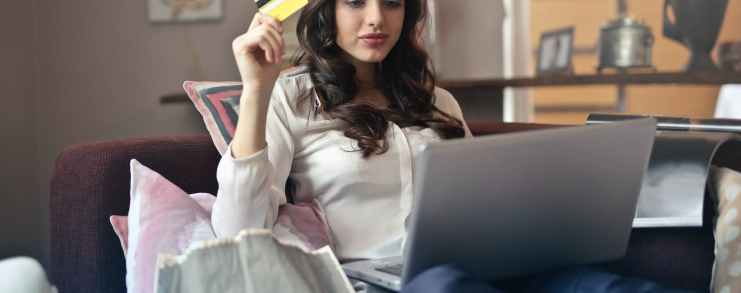 woman holding card while operating silver laptop