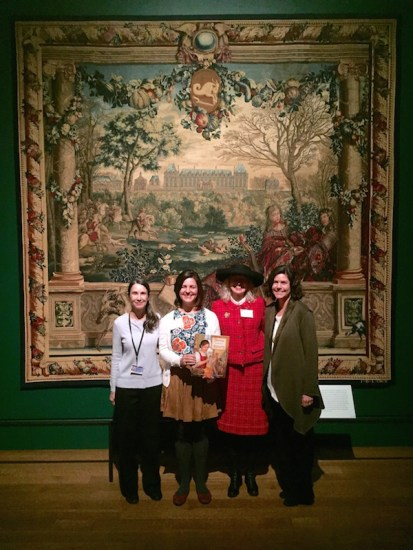 Photo of tapestry curator, author, illustrator, and editor in front of The Getty's version of the Chateau of Monceau/Month of December Tapestry