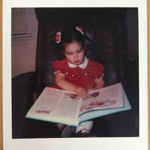 photo of Author Alexandra S. D. Hinrichs with a giant book around age 3