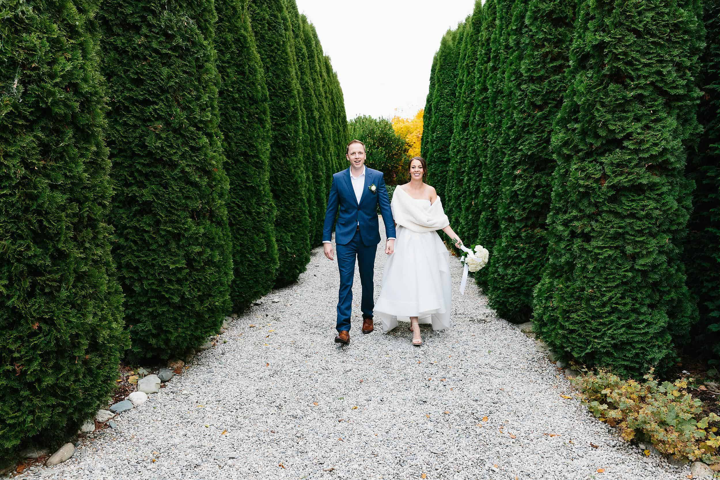 Bride and groom walk down tree lined driveway