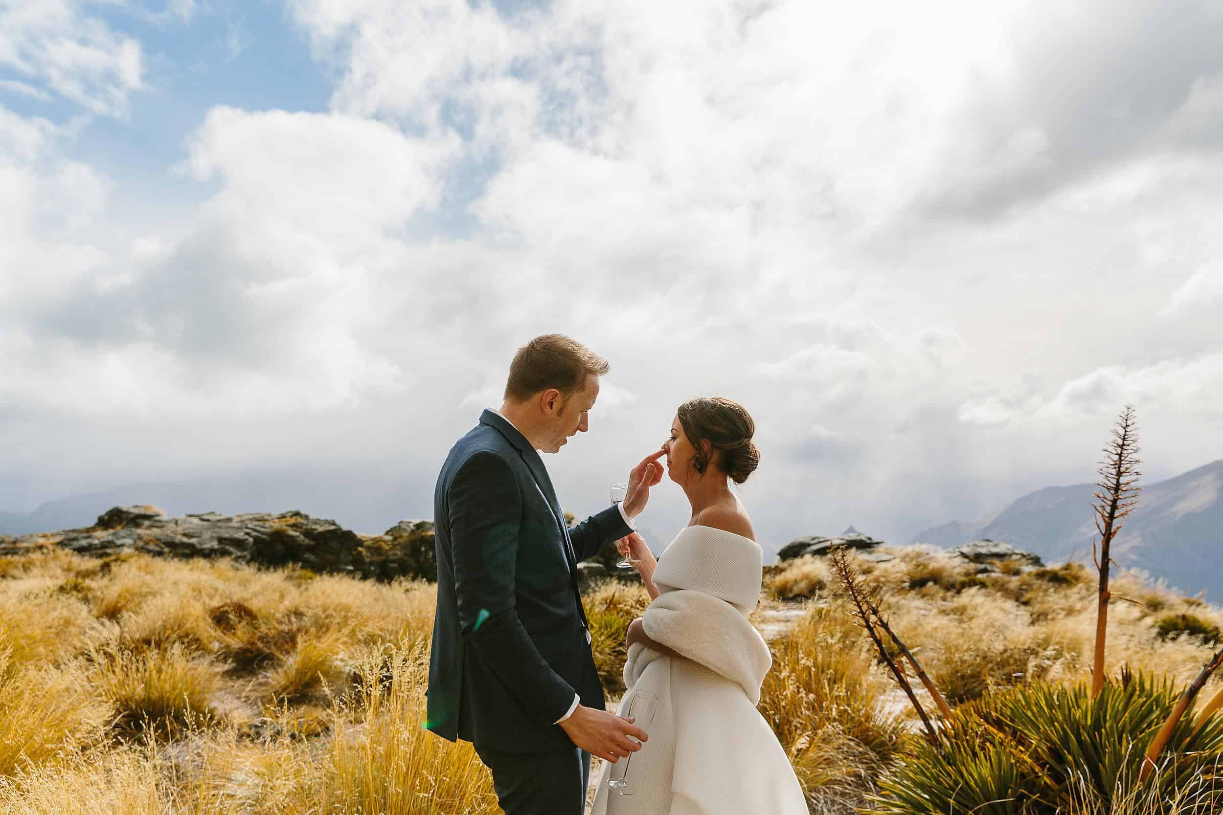 Groom picks brides nose on top of Cecil Peak, New Zealand