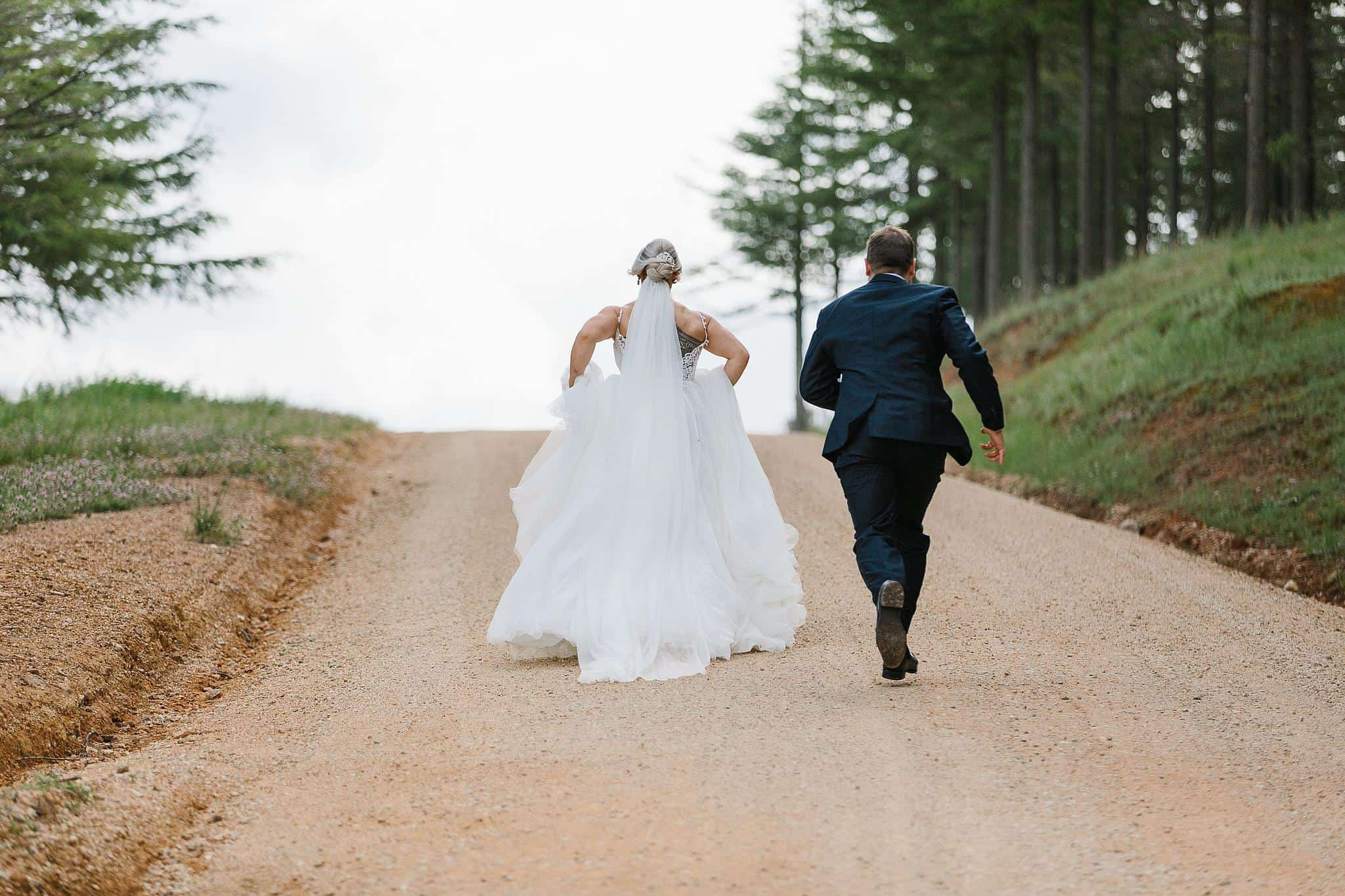 Bride and groom run up a hill