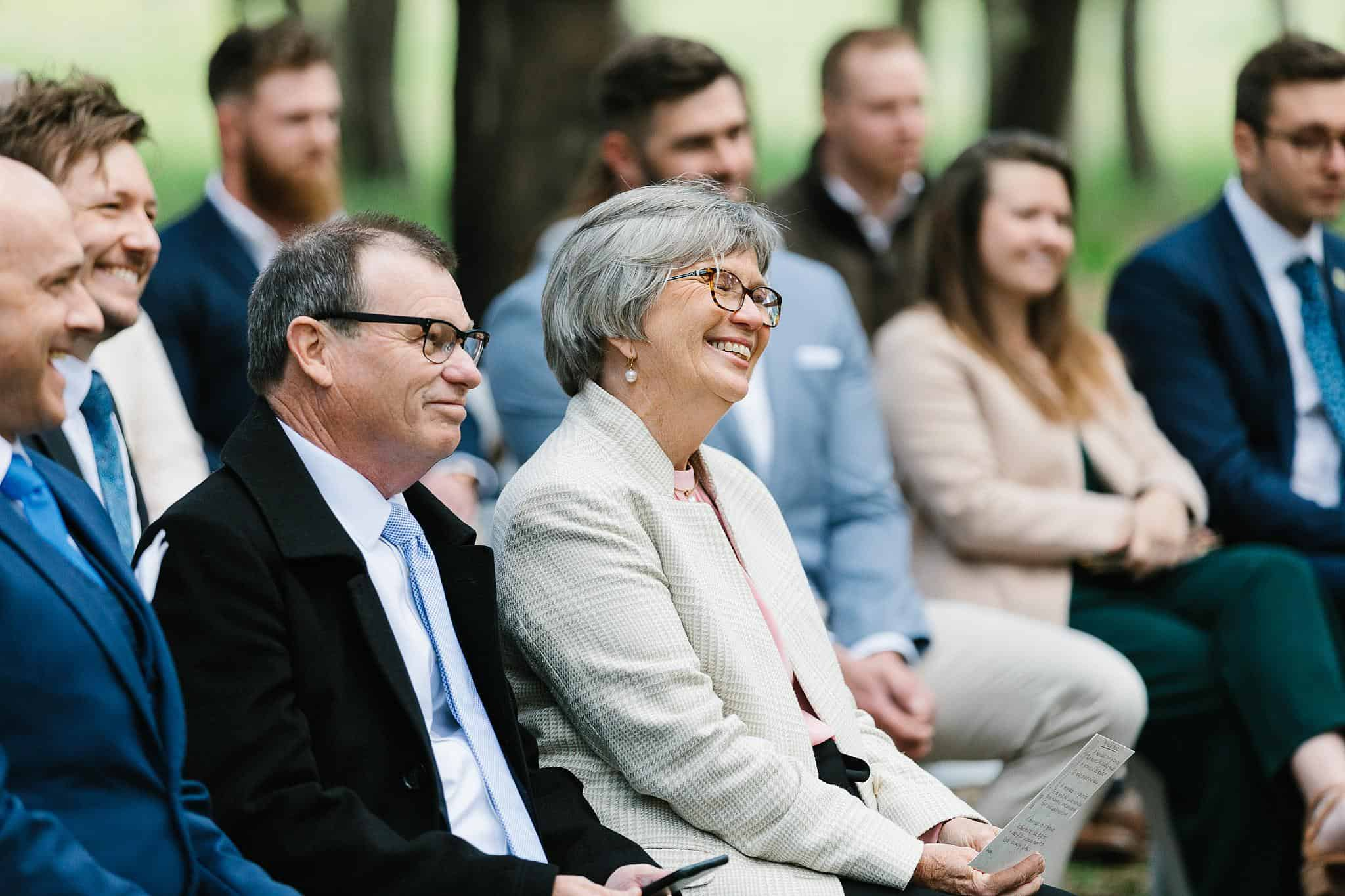 Mother of the groom smiles at couple