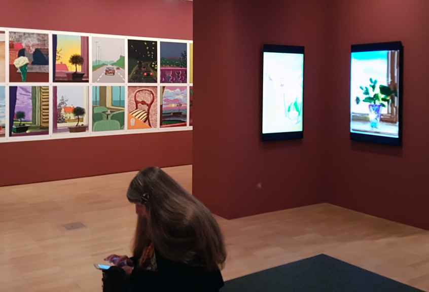 Image of display of printed digital drawings and two screens displaying work by David Hockney