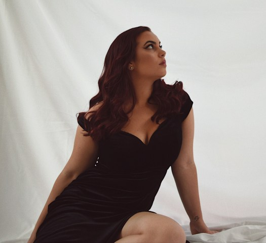 Giovanna Crescenzo wearing a black dress and looking up to the right.