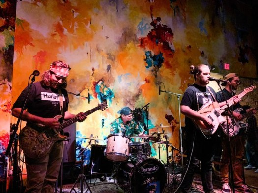 Old Old playing a show with a swirling, colorful paint splatter background.