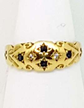 Four small black sapphires inset on 9ct gold ring in cross pattern