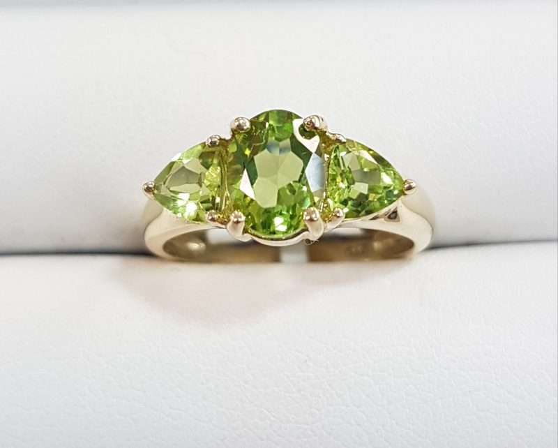 9ct gold ring featuring large oval faceted peridot with two triangular shaped peridot gems either side