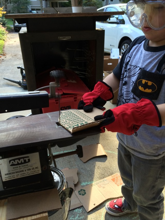 boy sawing cardboard