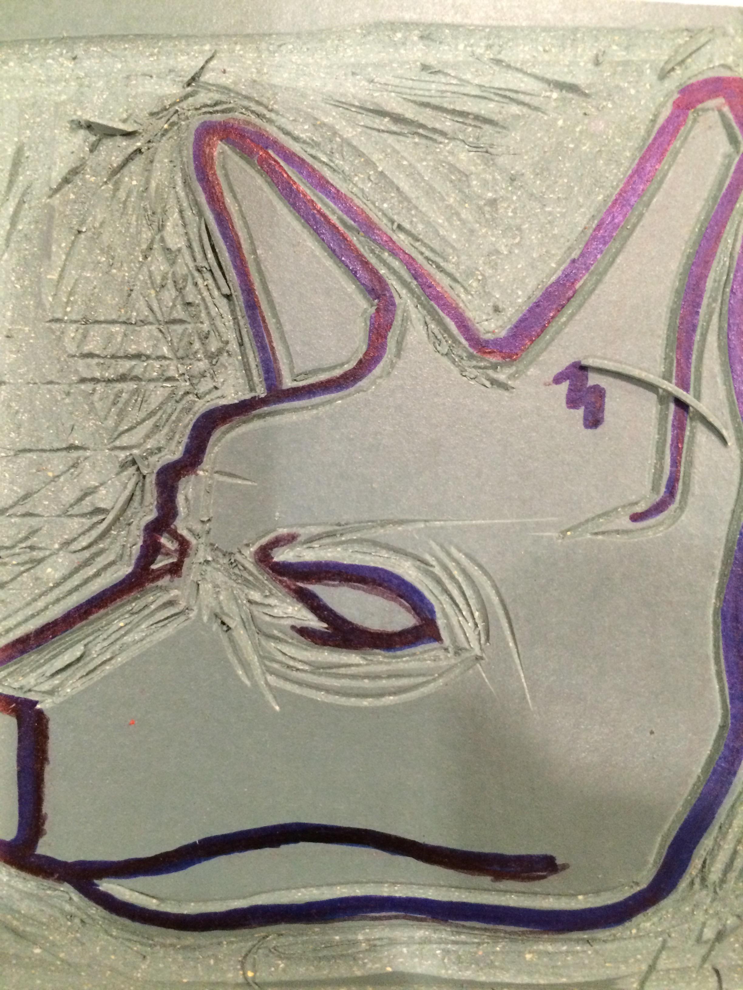 Blade carving details of dog into linoleum plate.