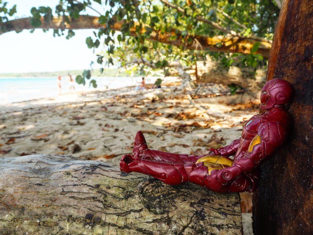 iron man figurine sitting on the beach