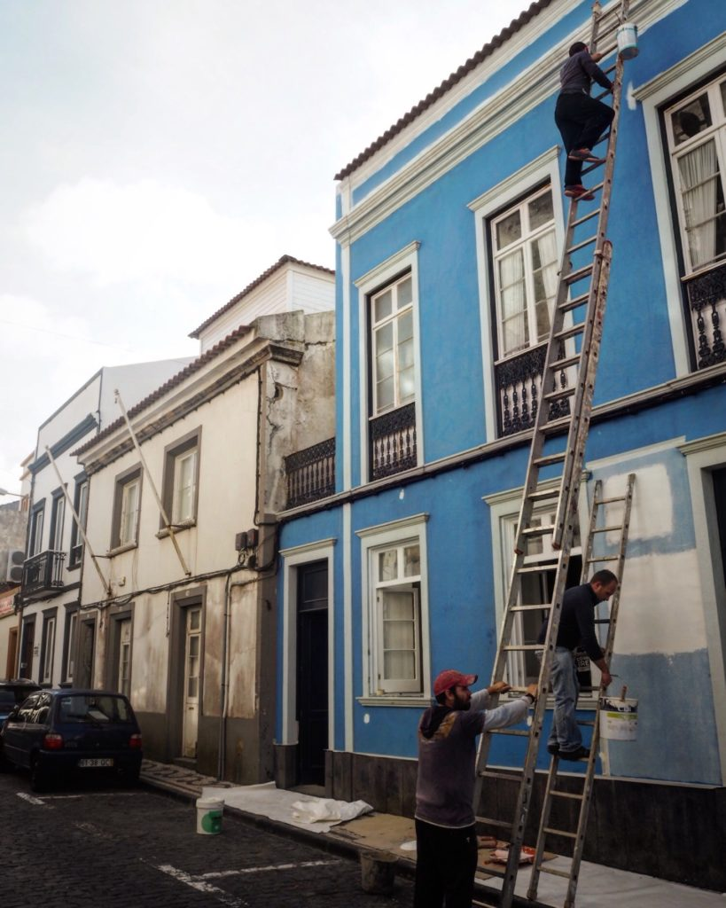 men on ladder outside a blue house in The Azores