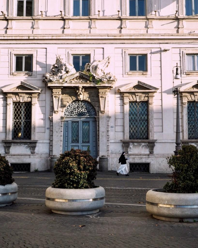 a nun walks past a building in Rome