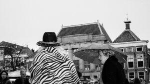 Vrouw met hoed en een vrouw met paraplu trotseren een winters bui in de stad Groningen.