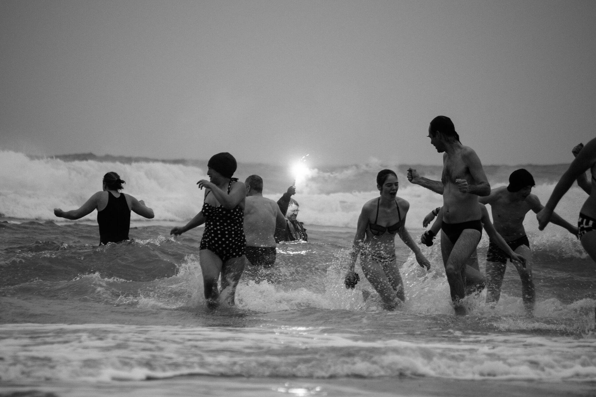 Deelnemers van de Nieuwjaarsduik Terschelling in het water bij Midsland aan Zee.
