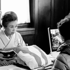Een oudere Japanse vrouw in kimono praat met een bezoekster.