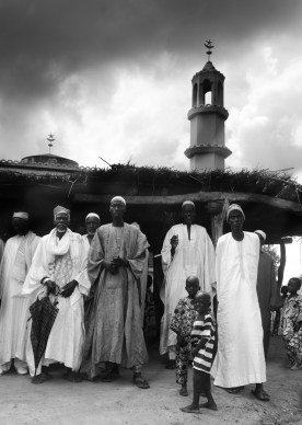 The older men of the village leave the mosque after praying.