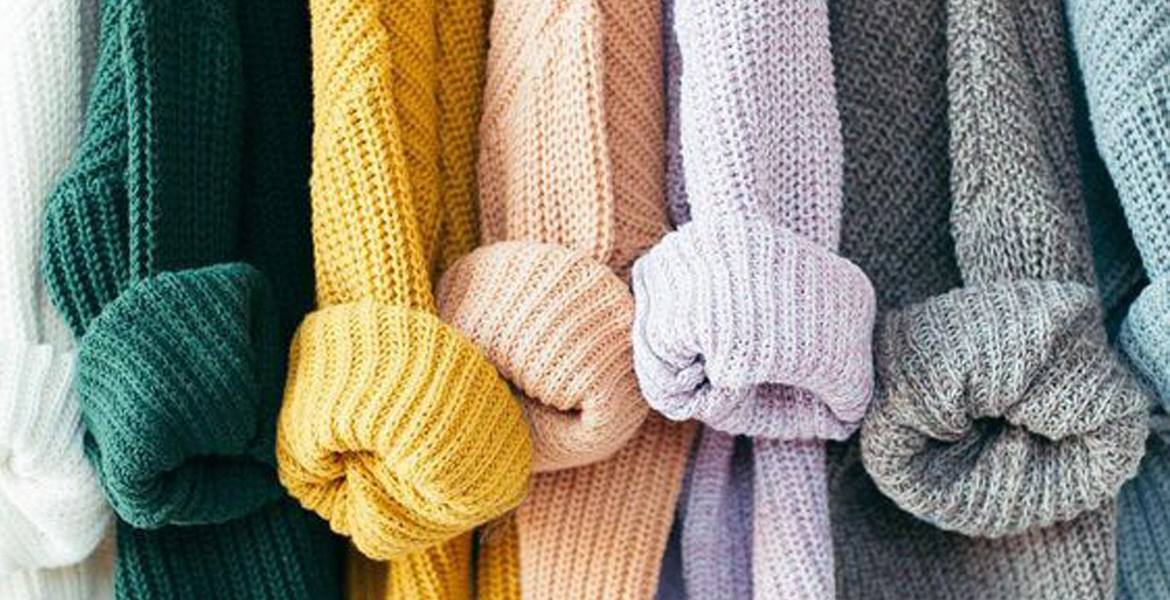 A rainbow of knitted long cardigans in white, green, yellow, peach, lilac, grey and blue