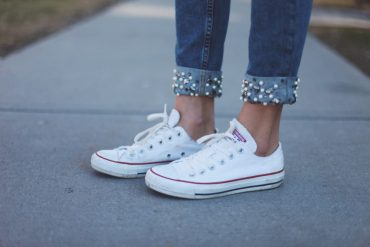 Woman wearing jewelled jeans and white Converse