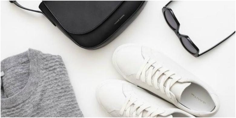 Grey jumper, black handbag, white trainers and black sunglasses