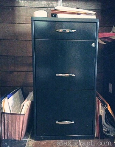 A black metal filing cabinet with papers on top and folders learning against each side