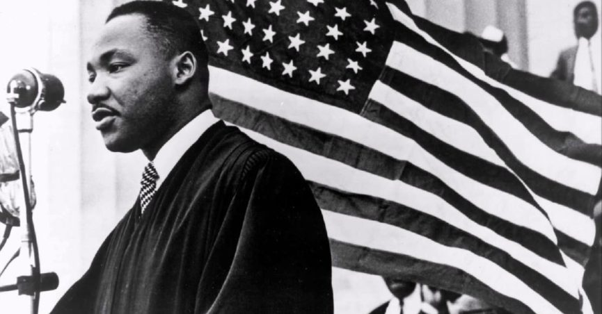 Dr. Martin Luther King, Jr. speaking in front of a flag
